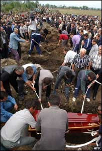 A coffin is buried as other graves are dug in Beslan