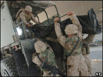 US marines load the body of a killed colleague into a truck
