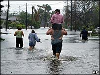 Christian Ferrer carries his wife, Pricila, on his shoulders through the floodwaters in the Pineapple Park neighbourhood of West Palm Beach, Florida on Sunday
