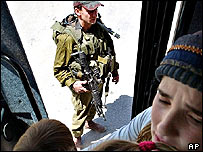 Settlers aboard a bus, watched by an Israeli soldier