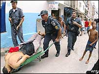 Police wheel off the corpse of a man killed in Rocinha on Monday