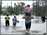 Christian Ferrer carries his wife, Pricila, on his shoulders through the floodwaters in the Pineapple Park neighbourhood of West Palm Beach, Florida following Hurricane Frances