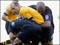 Wasps' Lawrence Dallaglio is wrapped up by the Saracens cover