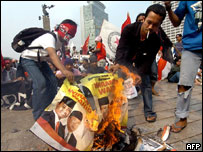 University students burn campaign posters during the July 2004 elections