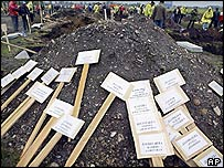 Temporary grave markers bear the names and dates of the victims being buried in Beslan