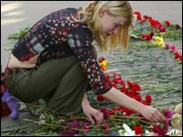 A girl weeps while laying flowers for Beslan victims