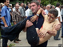 Wounded boy is carried from school during assault