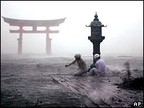 Priests of Itsukushima shrine inspect a stone lantern under torrential rain strong wind in Miyajima, western Japan, Tuesday, Sept 7