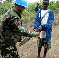 Lurd rebel hands in his rocket-propelled grenade to a Bangladeshi peacekeeper