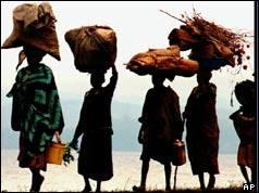 Rwandan refugees carrying bundles on their heads