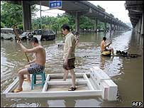 Residents use makeshift rafts to make their way through a flooded road in Chongqing 07/09/04