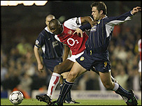 Arsenal captain Patrick Vieira battles for possession with Leeds' Mark Viduka