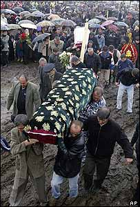 Ossetian men carry one of many coffins
