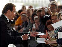Sir Roger Moore signing autographs