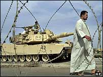 A man passes a US tank in Iraq