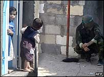 Palestinian children watch as a Hamas militant takes a rest during clashes near the Jabaliya refugee camp