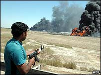 A Sunni insurgent shoots at a burning US military tanker in Abu Gharaib.