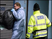 Police remove bags from a Manchester premises