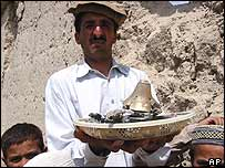 A tribal resident shows remains of artillery which damaged his home in Wana, Pakistan,  August 2004