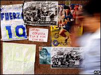 Una mujer pasa frente a afiches en apoyo de Maradona