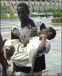 A disabled man is carried to a shelter in Kingston, Jamaica