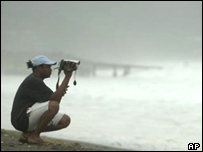 An unidentified Jamaican man films large waves in Kingston, Jamaica