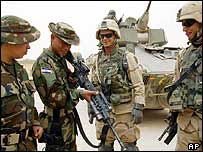 Honduran troops (L) discuss weapons near Najaf this April