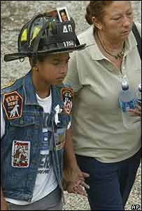 Youngster wearing firefighter's hat leaves Ground Zero