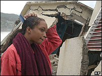Jamaican girl surveys the damage to her house