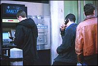 Человек с мобильным телефоном в очереди к банкомату
