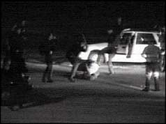 black and white freeze frame shows two officers wielding batons against man on ground