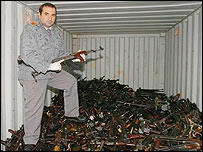An Italian finance police officer stands in a container where thousands of weapons were found
