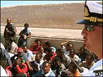 Migrants are supervised by an Italian naval officer. Archive picture