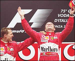 Michael Schumacher congratulates his team-mate as their one-two gives the constructors' title to Ferrari