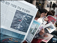 South Korean passengers in a subway train read newspapers reporting an explosion in North Korea - 13/9/04