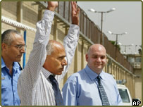 Mordechai Vanunu waves as he is escorted outside Shikma Prison