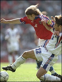 Karel Poborsky of the Czech Republic vaults a challenge from France's Bixente Lizarazu as Marcel Desailly looks on in their Euro 96  semi-final