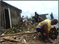 A Jamaican family cleans up after Hurricane Ivan