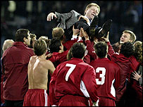 Latvia's players hold up their coach Aleksandrs Starkovs after securing their Euro 2004 place