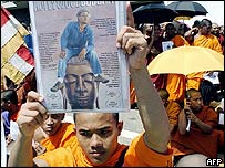 A Sri Lankan Buddhist monk holds aloft a poster for the movie Hollywood Buddha