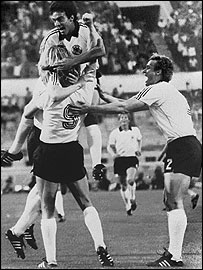 Hans Muller jumps on Horst Hrubesch, scorer of two goals in West Germany's 2-1 European Championship triumph over Belgium