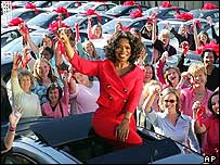 Talk show host Oprah Winfrey sits atop a Pontiac G6 surrounded by some of the winners