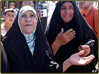 Women weep at the scene of a massive explosion outside a police station at the end of Haifa Street, Baghdad