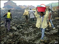 People walk with their belongings across lava fields in Goma (AP)