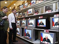 Russians watch President Putin's speech on televisions in a shop
