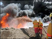 Firefighters try to contain an oil pipeline fire after an attack by insurgents near Baiji, northern Iraq