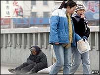 Teenagers walk past an elderly woman in Beijing