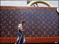A scavenger walks past a big luggage-like advertisement for a new Louis Vuitton  shop in Shanghai, 9/09/04