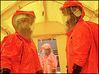 Firefighters inside a decontamination shower unit
