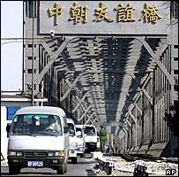 Chinese vans arrive in China from North Korea on a bridge that also carries rail traffic